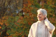 Happy elderly woman touchs her hair in nature. Happy senior woman enjoys a walk in autumnal nature stock photos