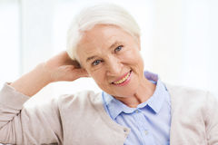 Happy senior woman face at home. Age and people concept - happy smiling senior woman at home Stock Photos