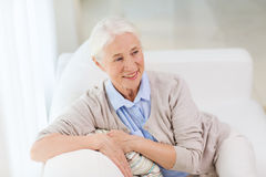 Happy senior woman face at home. Age and people concept - happy smiling senior woman sitting on sofa at home Stock Images