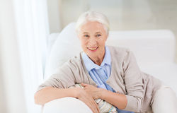 Happy senior woman face at home. Age and people concept - happy smiling senior woman sitting on sofa at home Royalty Free Stock Images