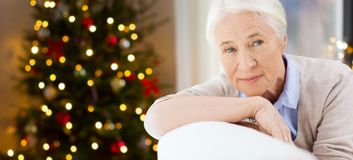 Happy senior woman face at home. Holidays, age and people concept - happy smiling senior woman at home over christmas tree lights background stock photography