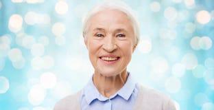 Happy senior woman face over blue lights Stock Photo
