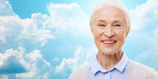 Happy senior woman face over blue sky and clouds. Age and people concept - happy smiling senior woman face over blue sky and clouds background Stock Images