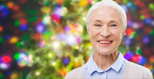 Happy senior woman face over christmas lights Royalty Free Stock Photography