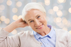Happy senior woman face over lights background. Age and people concept - happy smiling senior woman over holidays lights background Royalty Free Stock Photo