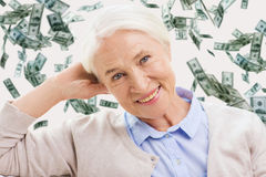 Happy senior woman face over violet background. Age, pension, finances, insurance and people concept - happy smiling senior woman over dollar money rain on Royalty Free Stock Photo