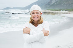 Happy senior woman feeling cold at beach Stock Photos