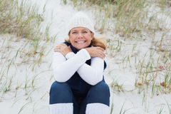 Happy senior woman feeling cold at beach royalty free stock photography