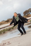 Happy senior woman frolicking on the beach Royalty Free Stock Images