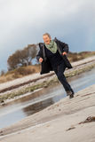 Happy senior woman frolicking on the beach Royalty Free Stock Image