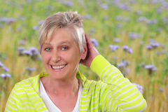 Happy senior woman in front of flower field Royalty Free Stock Photos