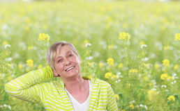Happy senior woman in front of flower field Stock Photography