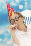 Happy senior woman with funny glasses a party hat and a noise maker. Happy mature woman with funny big eye-glasses , party hat and noise maker royalty free stock photos