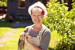 Happy senior woman in garden with shovel Royalty Free Stock Photos