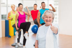 Happy senior woman gesturing thumbs up at gym Stock Image