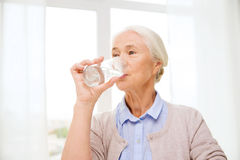 Happy senior woman with glass of water at home Stock Images