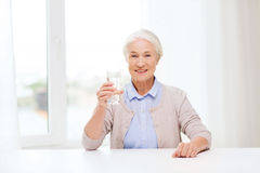 Happy senior woman with glass of water at home Stock Photography