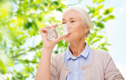 Happy senior woman with glass of water at home. Age, health and people concept - happy senior woman with glass of water over green natural background Stock Images