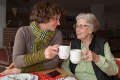Happy senior woman and granddaughter drinking coffee stock images