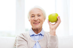 Happy senior woman with green apple at home Stock Photography