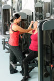 Happy senior woman at gym. Happy senior women at gym workout with personal trainer assistance stock photography