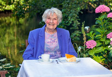 Happy Senior Woman Having Snacks at the Garden Stock Image