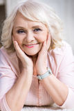 Happy senior woman with head on hands smiling at camera Royalty Free Stock Photo