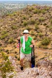 Happy Senior Woman Hiking. A happy senior woman hikes up a very steep hill in the Arizona desert. She is thrilled to have made it to the top. She is carrying two Royalty Free Stock Photography