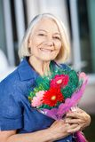 Happy Senior Woman Holding Bouquet At Nursing Home Royalty Free Stock Images
