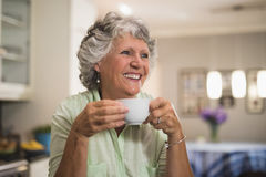 Happy senior woman holding cup at home Royalty Free Stock Photography