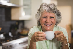 Happy senior woman holding cup at home Stock Image