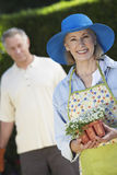 Happy Senior Woman Holding Flower Pot Stock Images