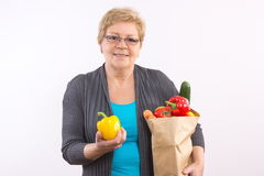 Happy senior woman holding fruits and vegetables in shopping bag, healthy nutrition in old age Royalty Free Stock Photo