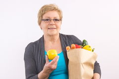 Happy senior woman holding fruits and vegetables in shopping bag, healthy nutrition in old age Stock Photo