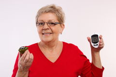 Happy senior woman holding glucometer and fresh cupcake, measuring and checking sugar level, concept of diabetes Stock Images