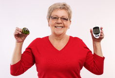 Happy senior woman holding glucometer and fresh cupcake, measuring and checking sugar level, concept of diabetes Royalty Free Stock Images