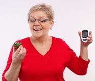 Happy senior woman holding glucometer and fresh cupcake, measuring and checking sugar level, concept of diabetes Stock Photo