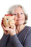 Happy senior woman holding piggy Royalty Free Stock Photo