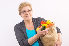 Happy senior woman holding shopping bag with fruits and vegetables, healthy nutrition in old age Royalty Free Stock Image