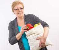 Happy senior woman holding shopping bag with fruits and vegetables, healthy nutrition in old age stock photography