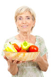 Happy senior woman holding vegetables stock photography