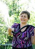 Happy senior woman hoses the garden Stock Images