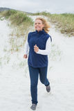 Happy senior woman jogging at beach Stock Photography
