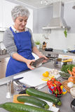 Happy senior woman in the kitchen preparing fresh fish. Royalty Free Stock Images
