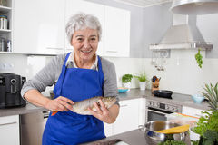 Happy senior woman in the kitchen preparing fresh fish. Royalty Free Stock Photos