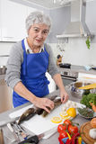 Happy senior woman in the kitchen preparing fresh fish. Stock Photos