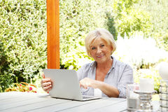 Happy senior woman with laptop. Portrait of senior woman relaxing at home. Retired female typing on computer while sitting in the garden and looking at camera Stock Photo