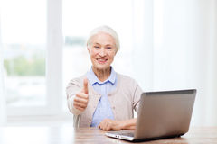 Happy senior woman with laptop showing thumbs up Stock Photography
