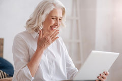 Happy senior woman laughing. Wonderful mood. Happy joyful senior woman looking at the laptop screen and laughing while being in a wonderful mood Stock Photography