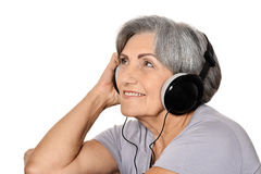 Happy senior woman listen a music in headphones isolated on whit Stock Photography